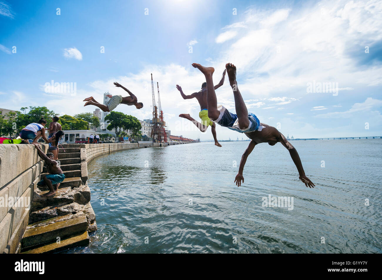 RIO DE JANEIRO - FEBRUARY 25, 2016: Young Brazilians jump into Guanabara Bay from a wall at Maua Plaza at Porto - Stock Image