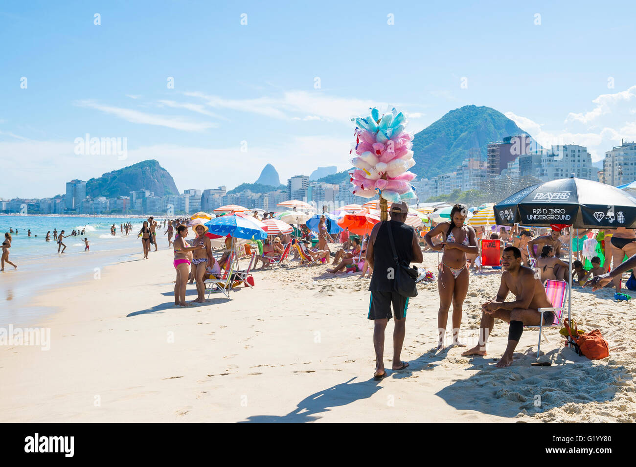 RIO DE JANEIRO - FEBRUARY 27, 2016: Brazilian beach vendor selling cotton candy floss with potential customers on - Stock Image