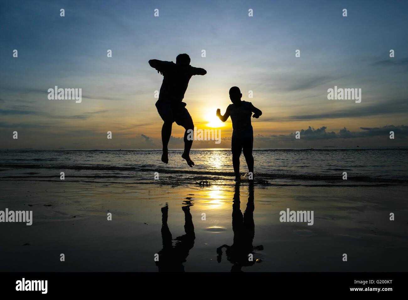 boys jumping on the beach Sunset Stock Photo