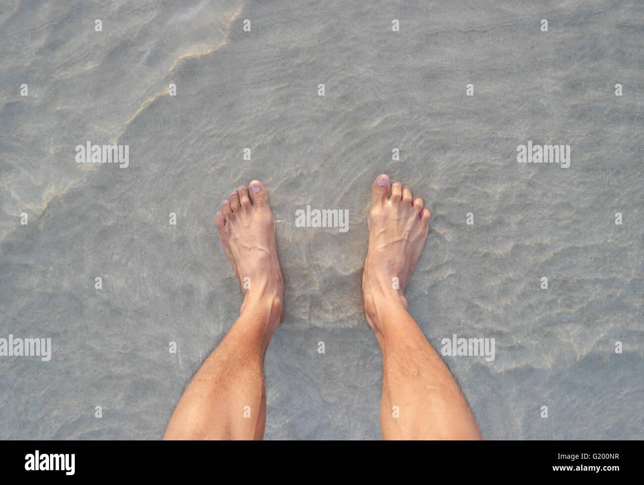 Men's feet on the beach. Stock Photo