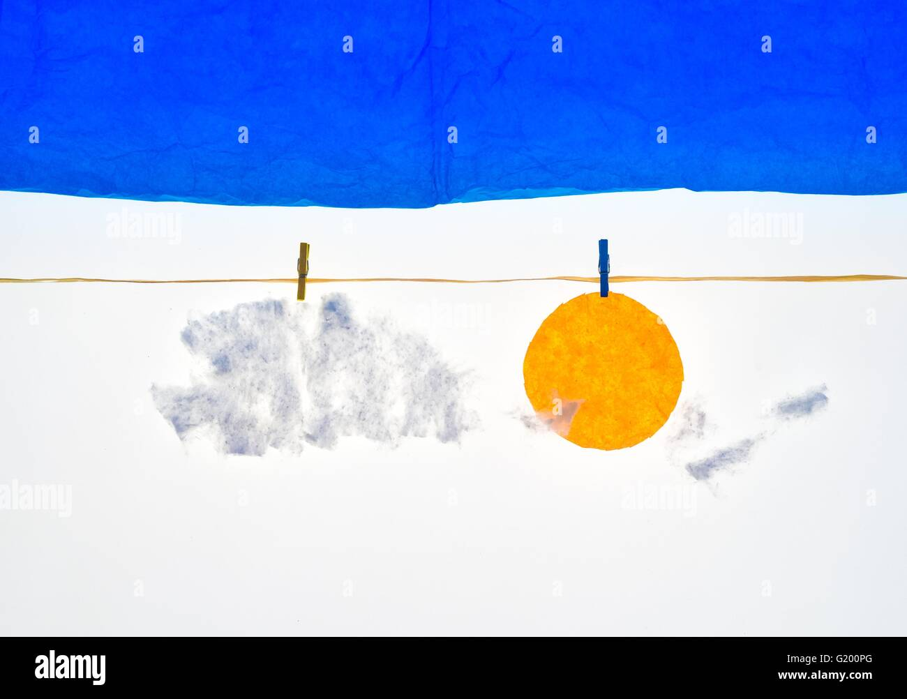 composition with clothes pegs and a fake sun and sky - Stock Image