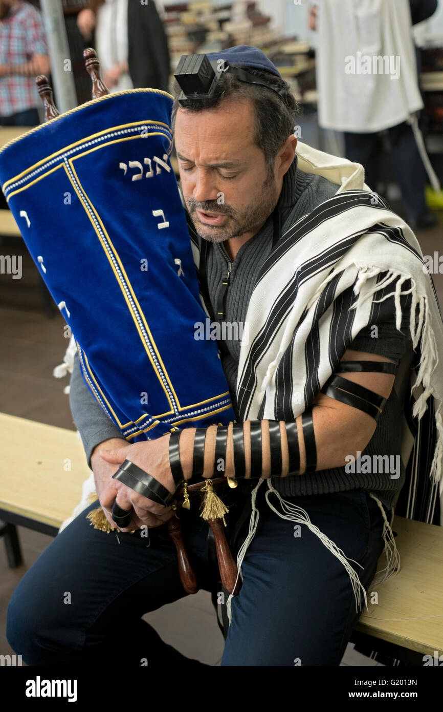 After a Torah reading and before it's returned to the Holy Ark, A reliigous Jewish man holds the Torah and recites - Stock Image
