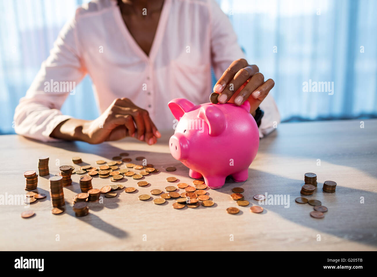 Woman putting money in a piggy bank Stock Photo