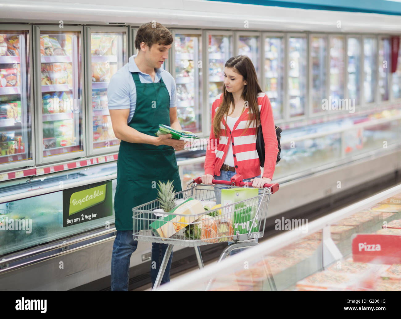 A man grocer advising his customer - Stock Image
