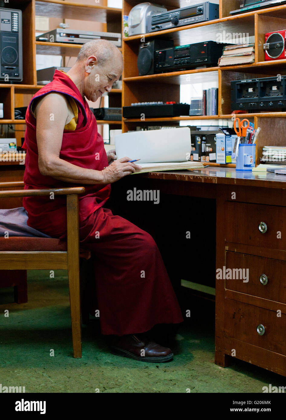 A monk works at the Tibetan Government Library and Archive collection.McLeod Ganj, Dharamsala,India - Stock Image