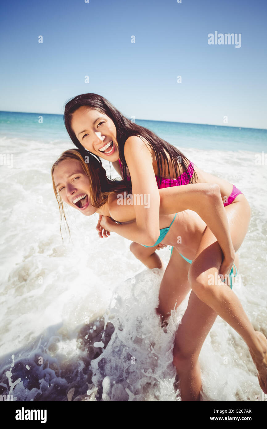 Woman giving piggy back to her female friend - Stock Image