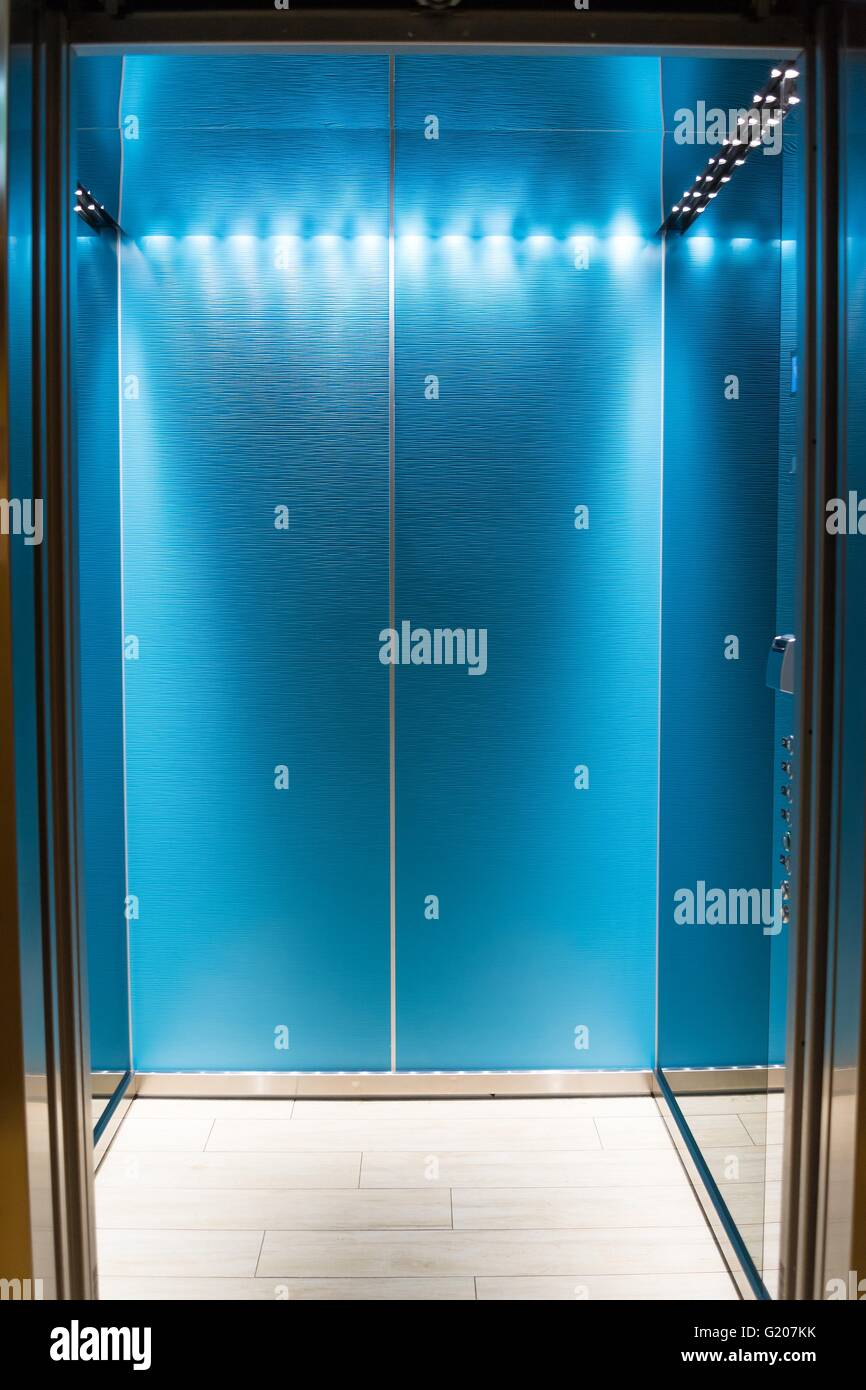 An empty modern blue elevator or lift with metal doors that are open in building with lighting. - Stock Image