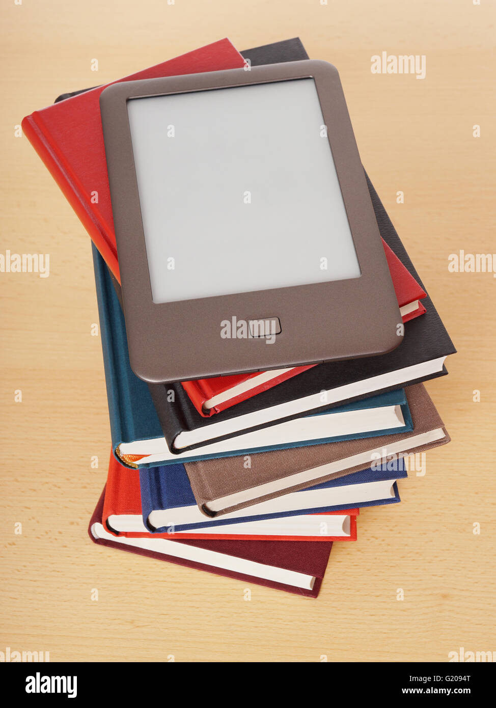 e-book reader on pile of books - Stock Image