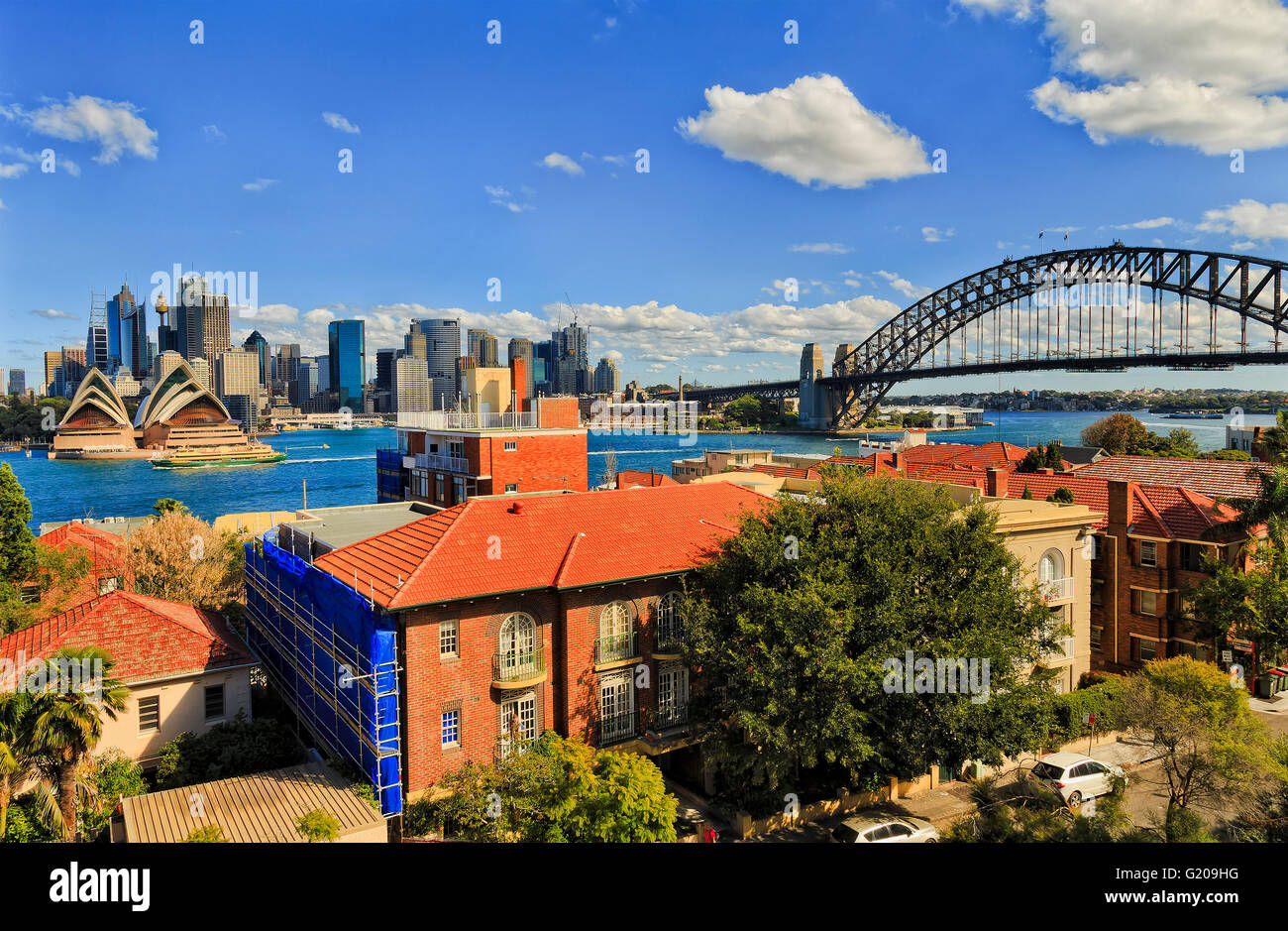 Sydney city landmarks with Harbour bridge and skyscrapers viewed across Harbour from Kirribilli above residential - Stock Image