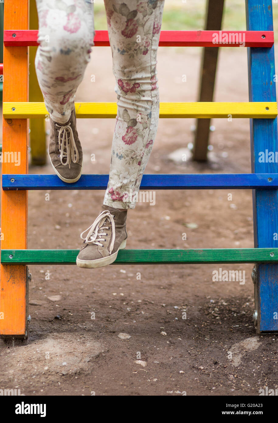 Woman's legs in the colorful children playground - Stock Image