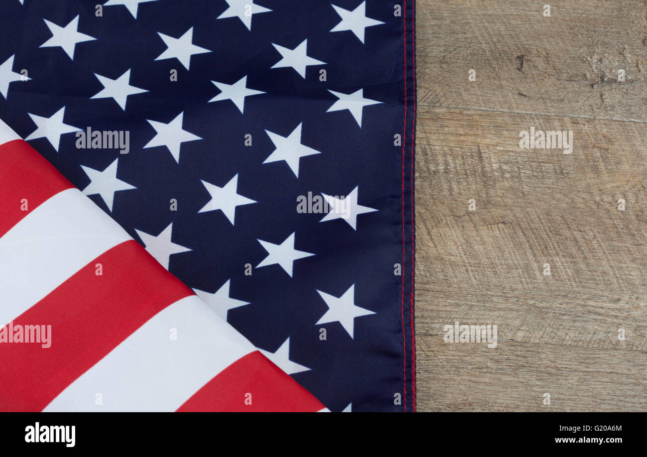 bd5381c13030 Fragment of American flag folded on wooden walnut table. Horizontal image  with copy space.