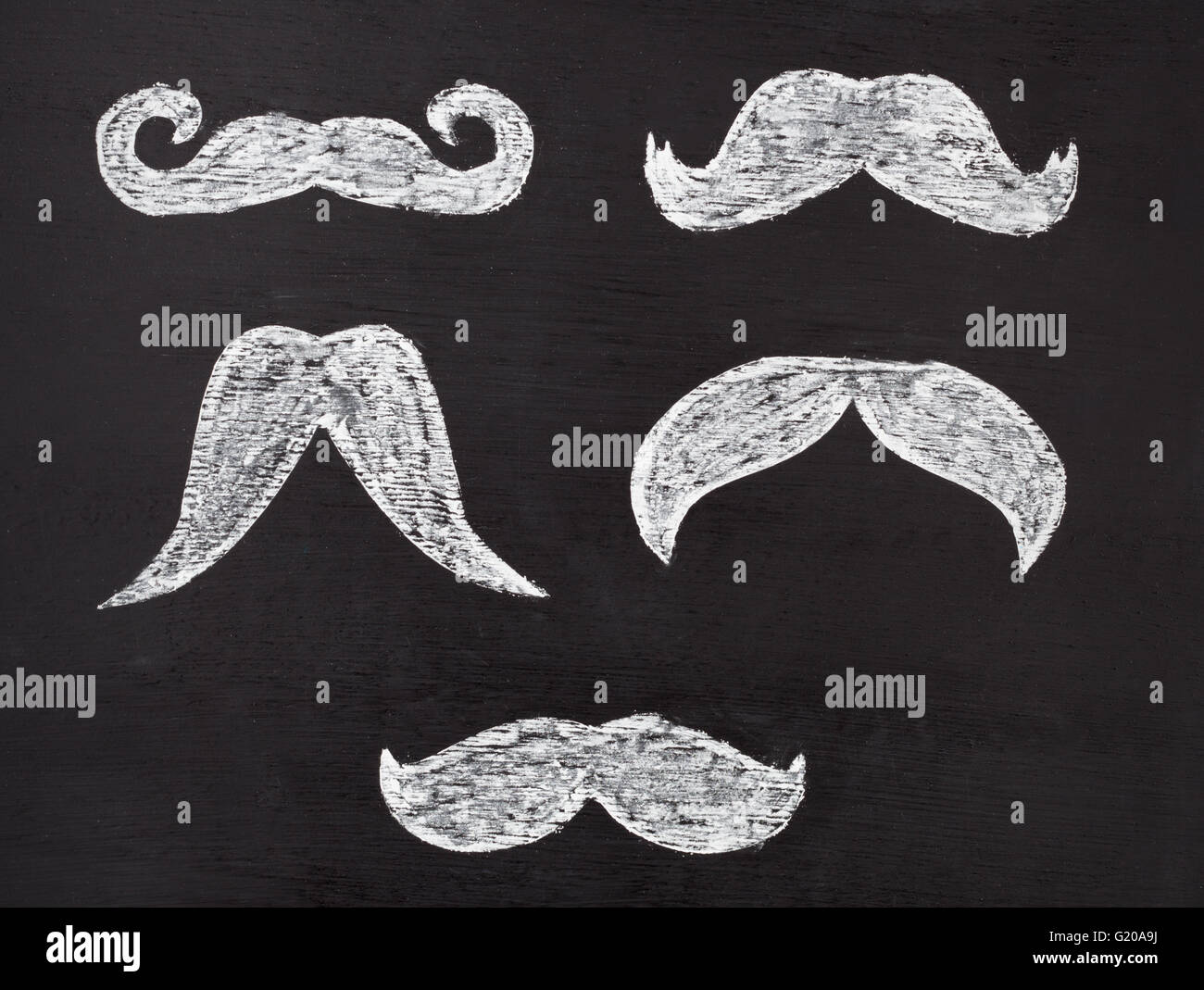 Set of white moustaches hand drawn with chalk on blackboard. Movember men's health awareness concept. - Stock Image