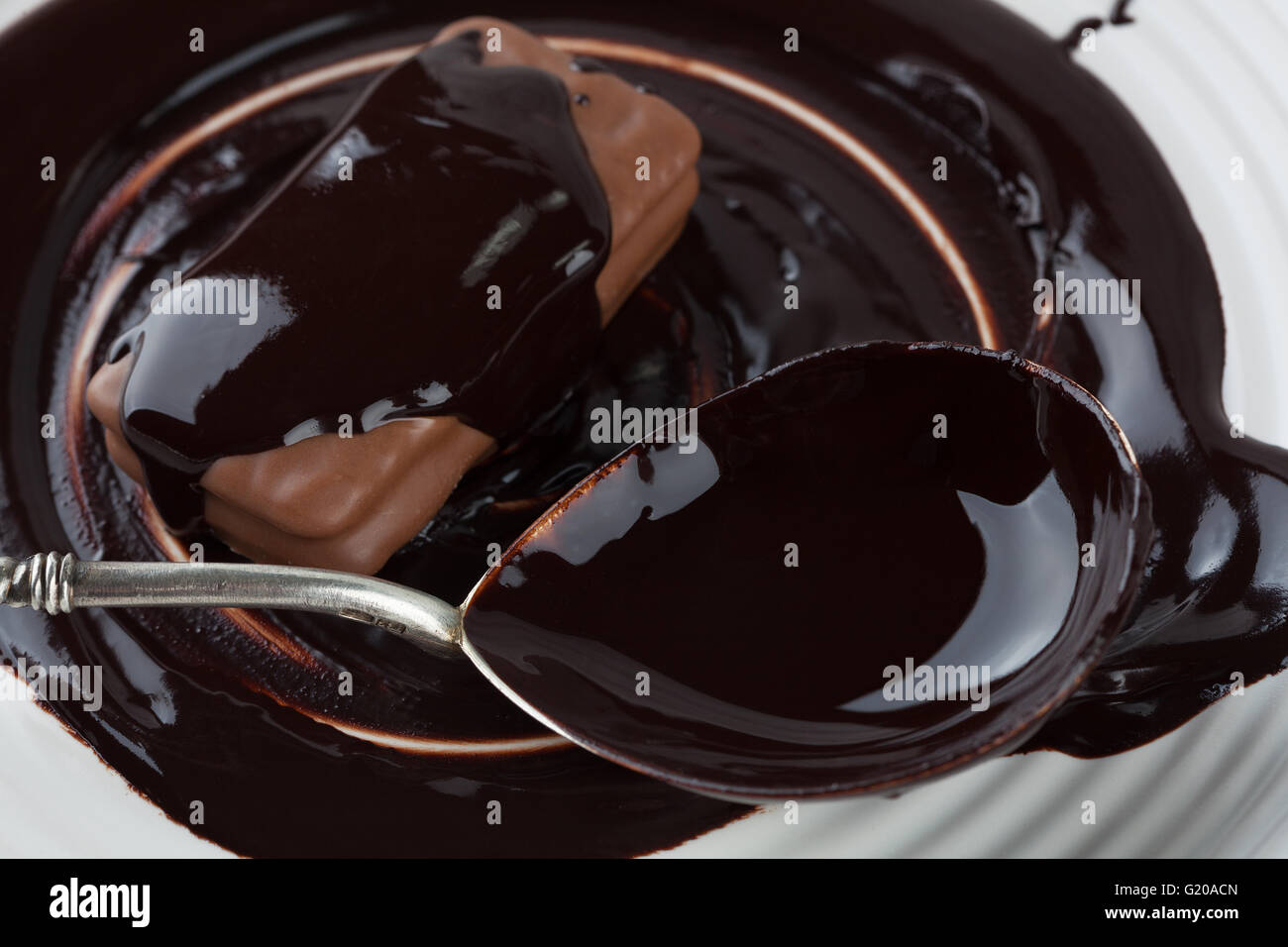 Closeup of cookie and silver spoon covered in dark melted chocolate on white plate - Stock Image