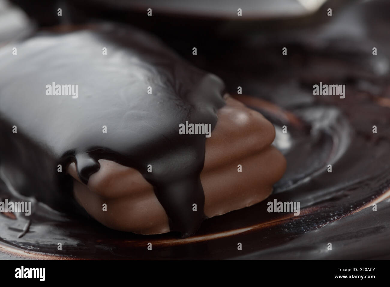 Extreme closeup of cookie covered in dark melted chocolate - Stock Image