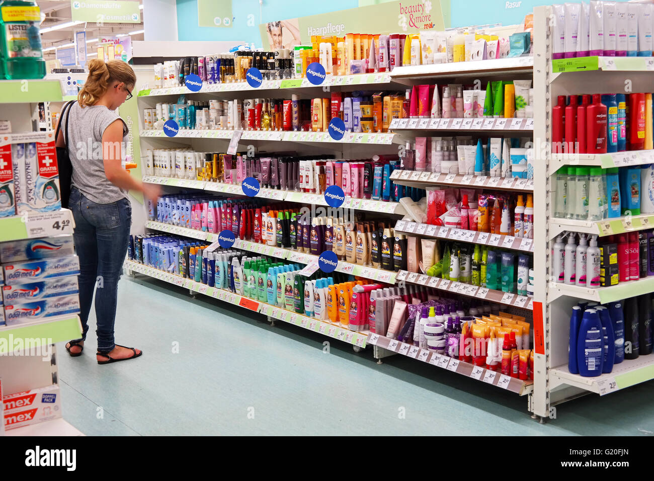 Young woman in front of shelves with toiletries in a Supermarket - Stock Image