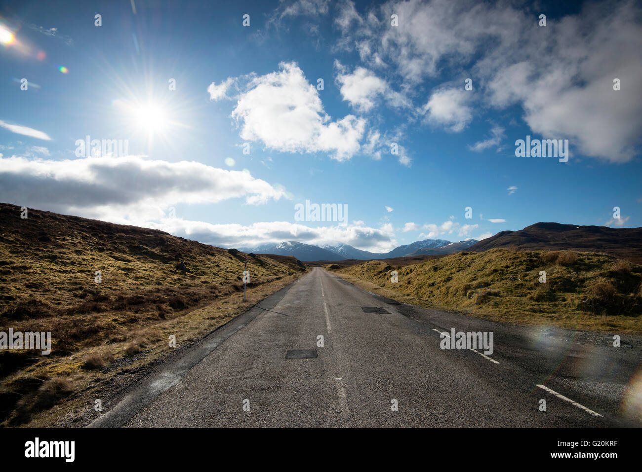 Fluffy white clouds and endless open road on the A832 in the far North West of Scotland, UK Stock Photo