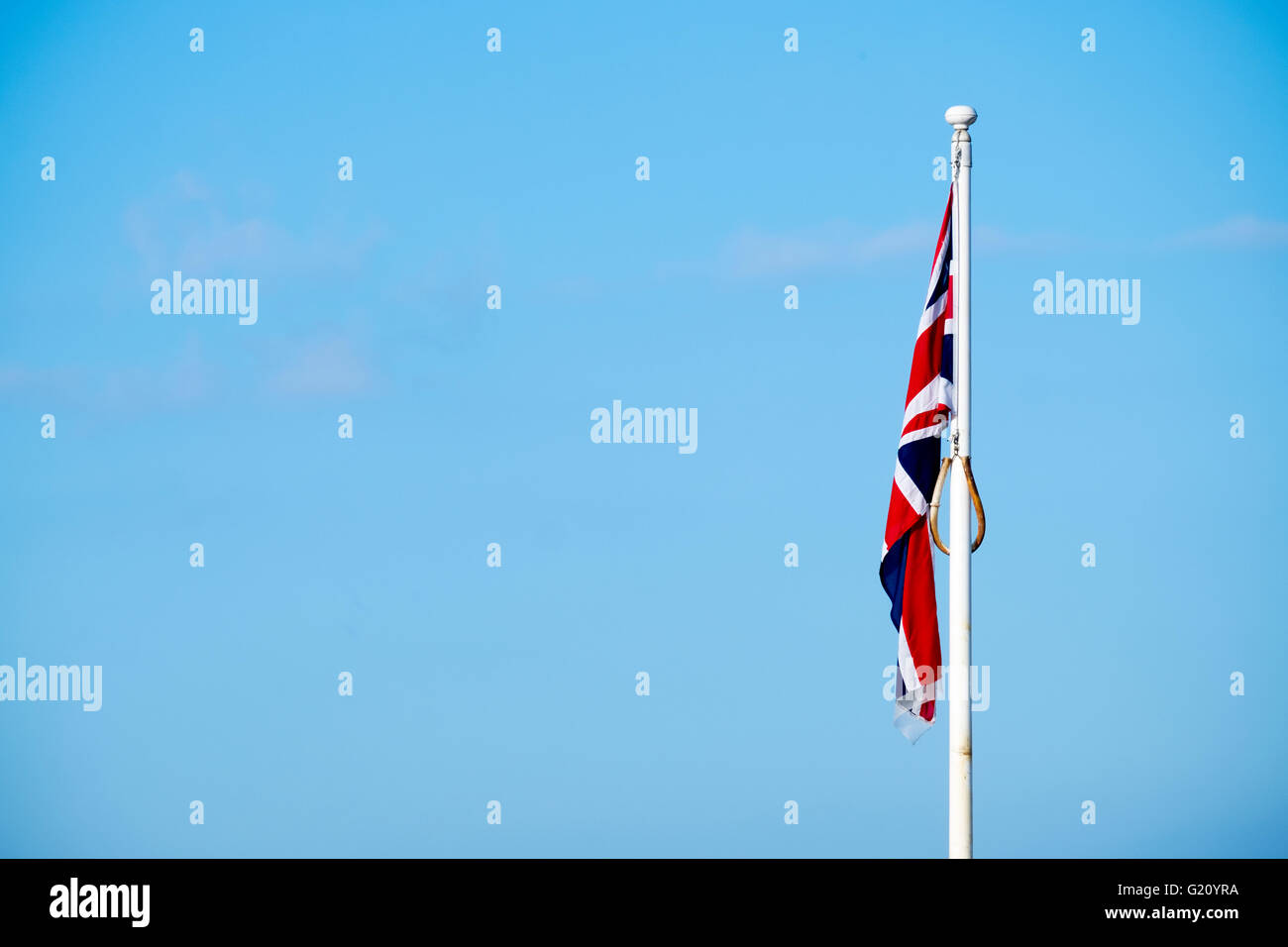 union jack flag flying slack with out wind on a windless day against a clear blue sky. - Stock Image