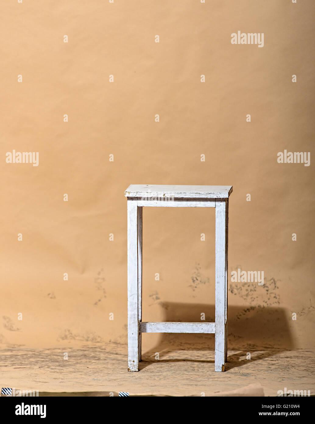White stool in studio on light brown background - Stock Image