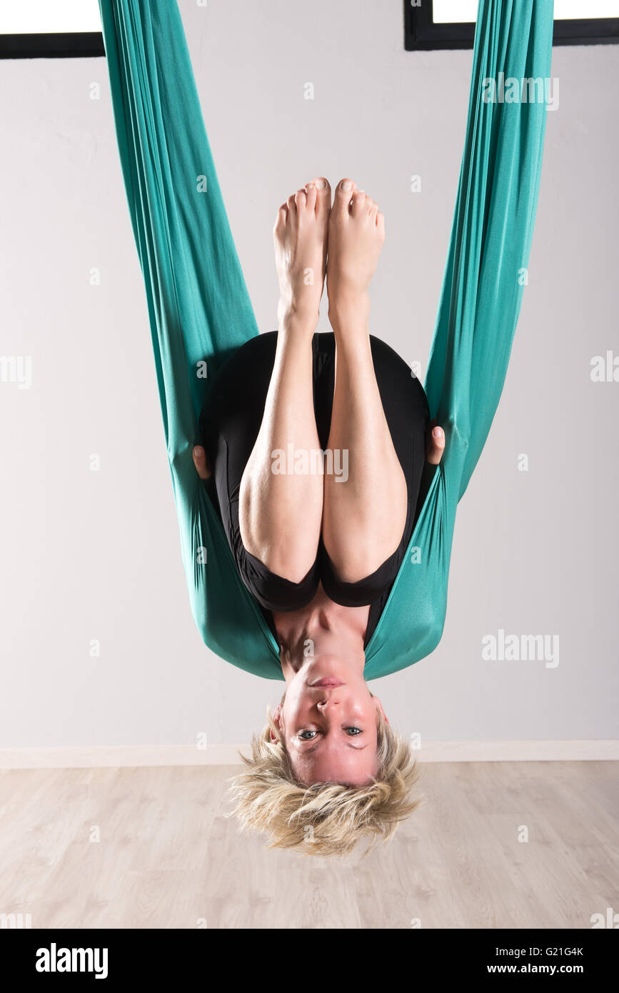 Serious blond young adult female hanging upside down with toes facing upward in green aerial yoga tarp - Stock Image