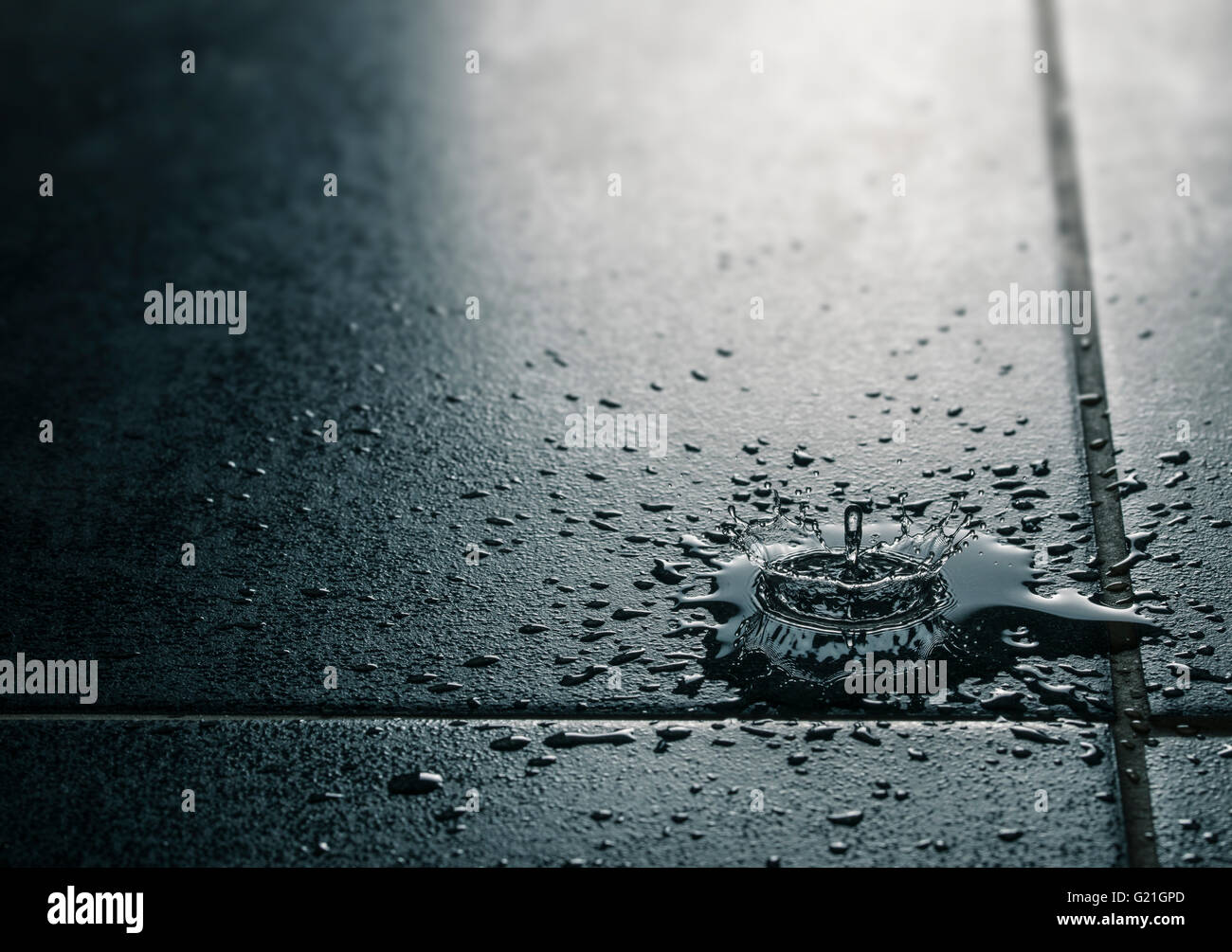 Water drips falling on a water resistant tile flooring. Black and blue tones with copyspace on the left side. Concept - Stock Image