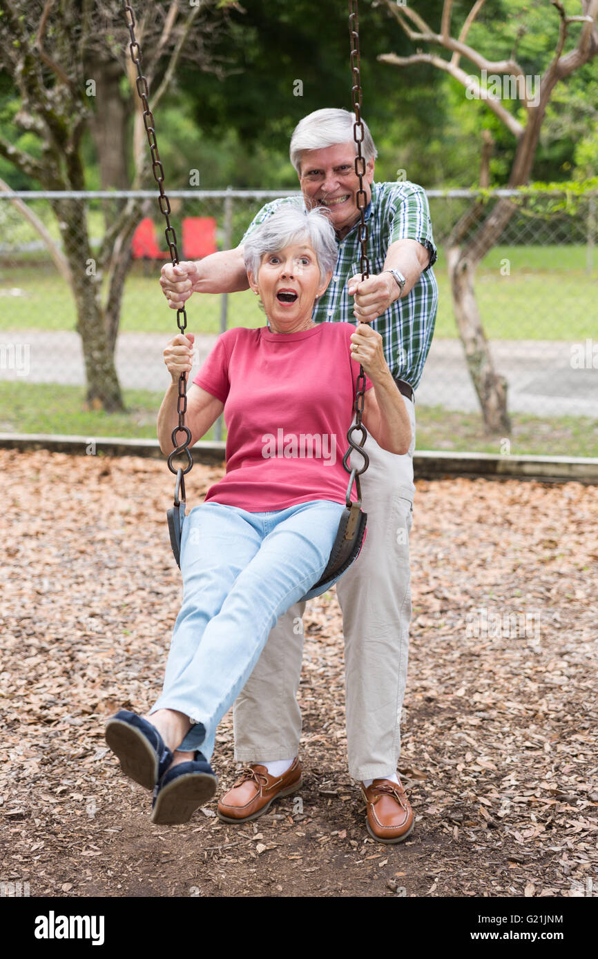 senior couple swinging in the park - Stock Image