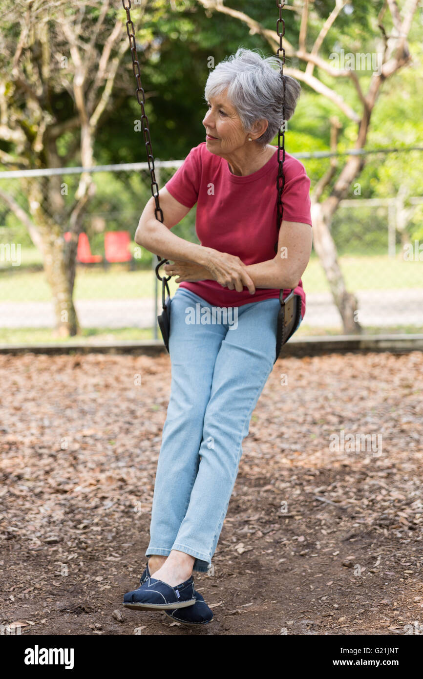 senior lady on a swing in deep thought contemplating relaxing - Stock Image