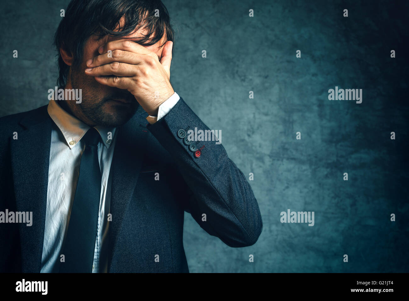 Unhappy businessman under stress after business project failure, hand covering eyes. - Stock Image