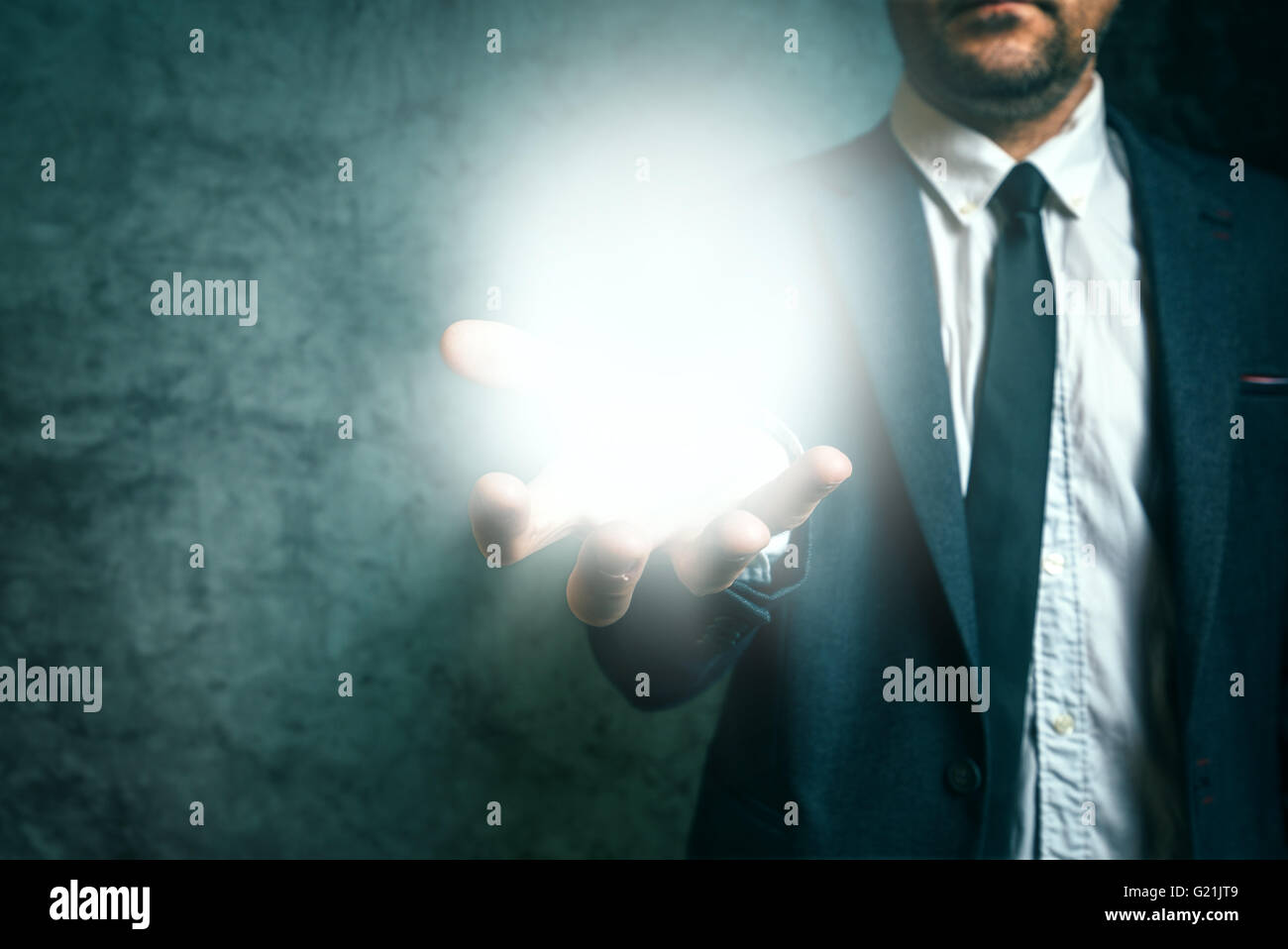 Business vision concept with elegant adult businessman holding bright light of new ideas in hand - Stock Image