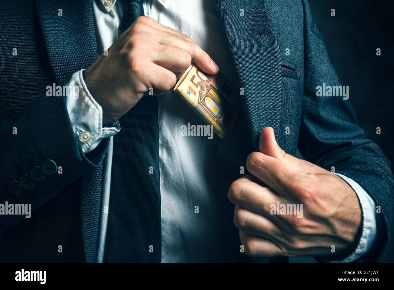 Money in pocket, businessman putting euro banknotes in suit pocket, bribe and corrupution concept. - Stock Image
