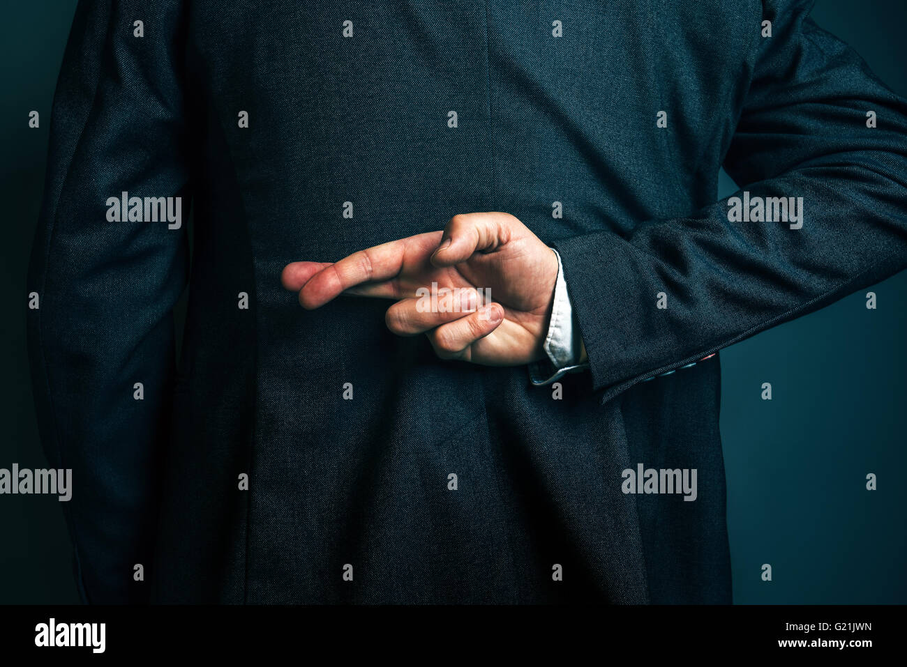Dishonest businessman telling lies, lying businessperson holding fingers crossed behind his back - Stock Image