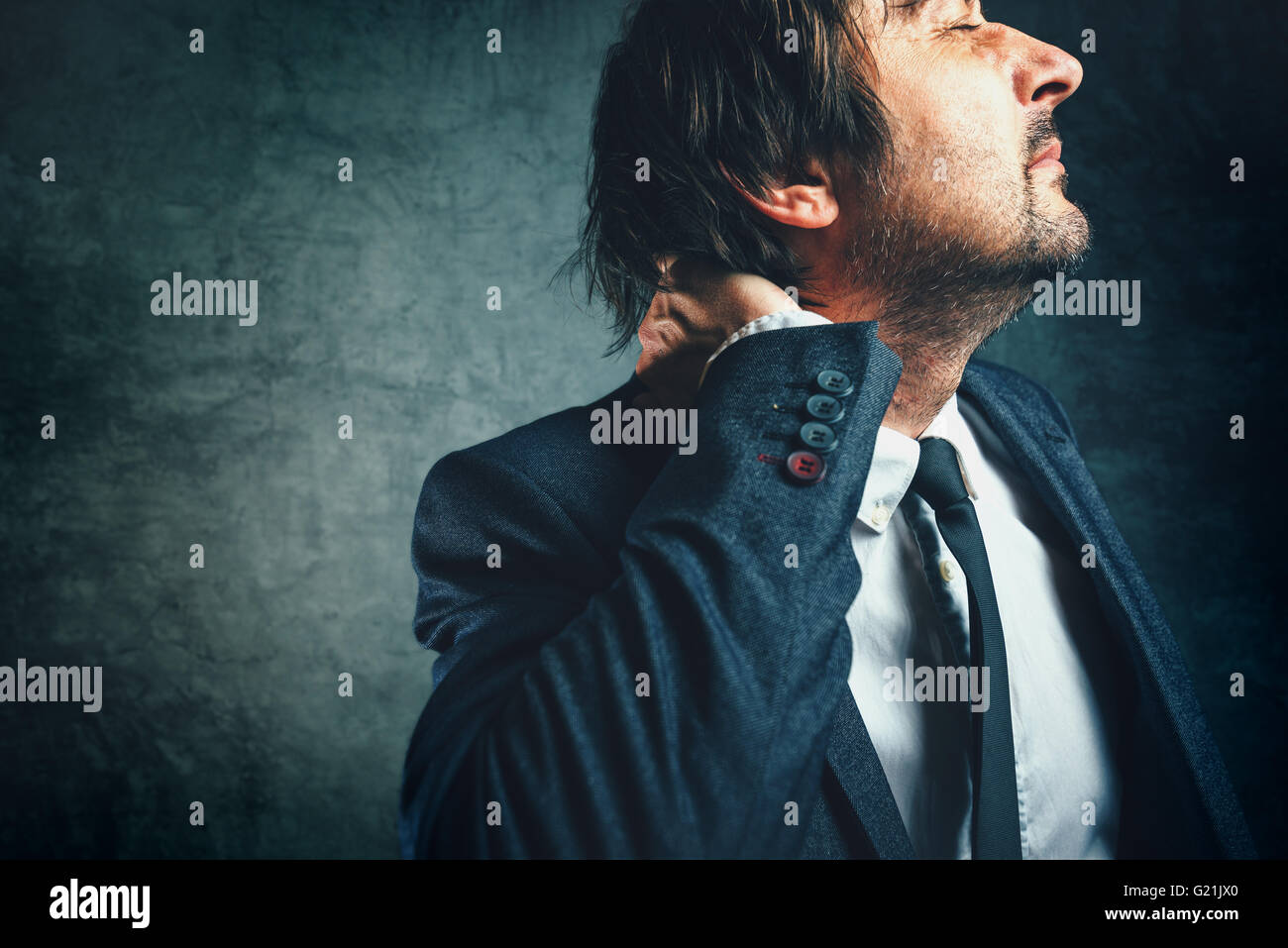 Pain in the neck of a businessman, stressed businessperson in elegant suit suffering from neckache. - Stock Image