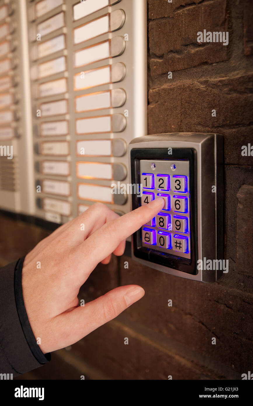 Woman dialing passcode on security keypad intercom to open entrance door of the apartment building. - Stock Image