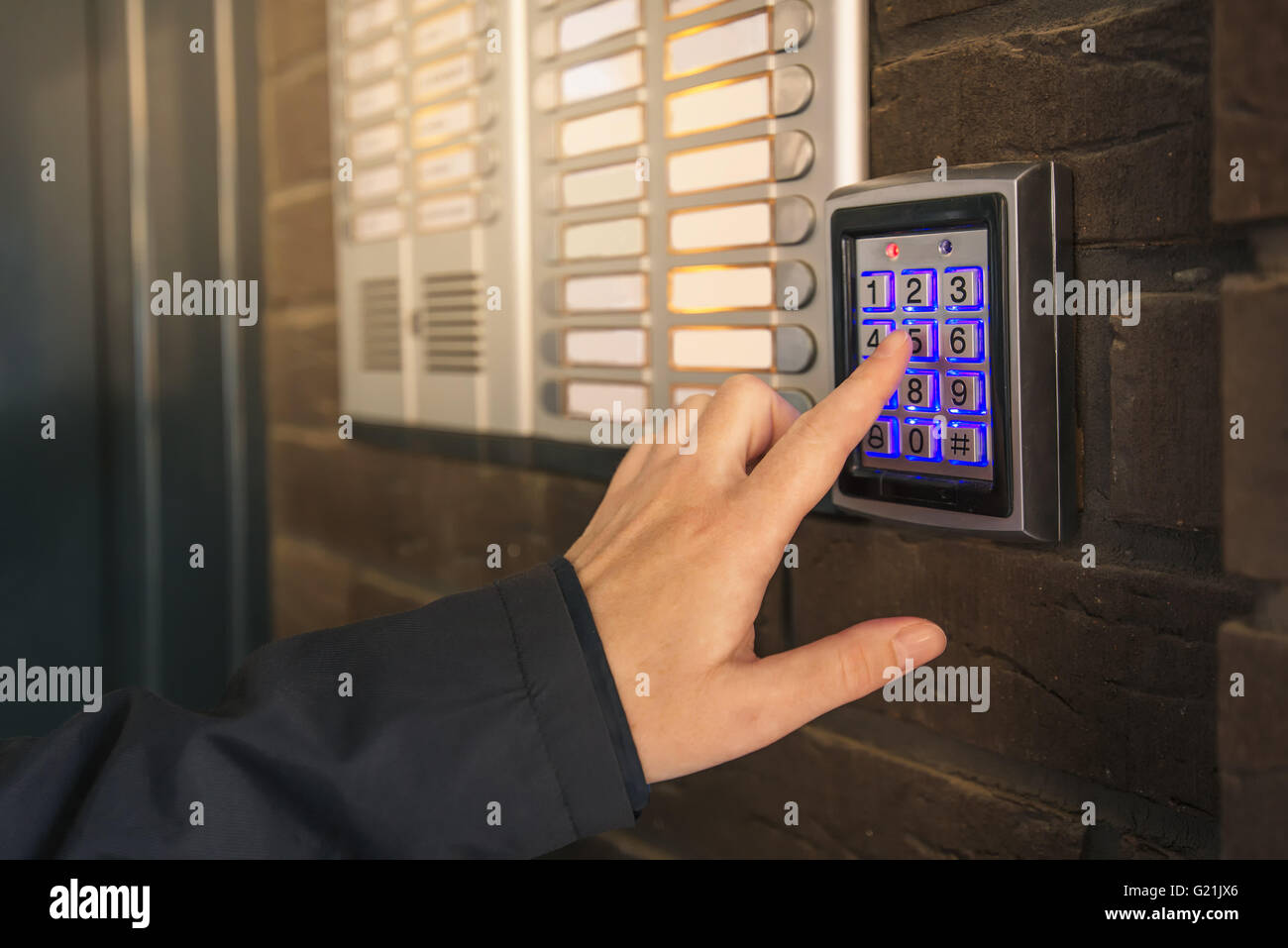 Woman dialing pass code on intercom security keypad to open entrance door of the apartment building. - Stock Image