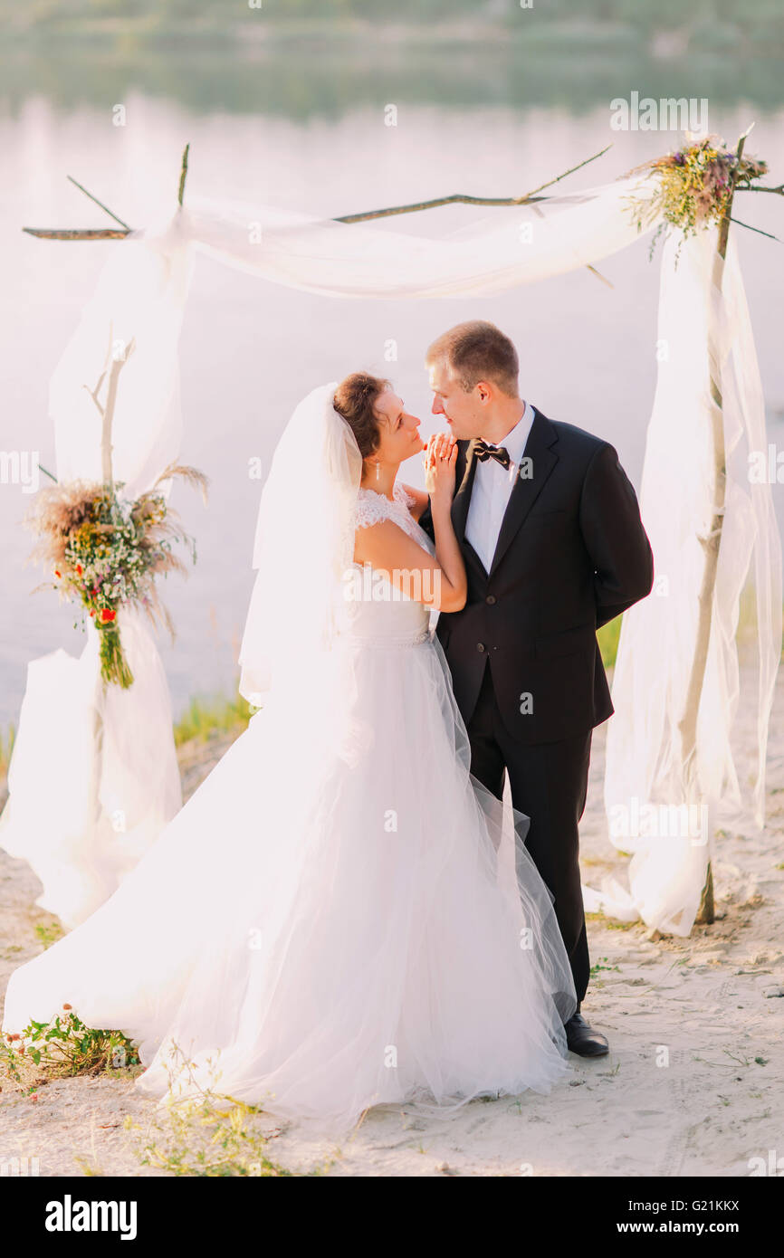 Beautiful bride in white dress and handsome groom wearing black suit ...