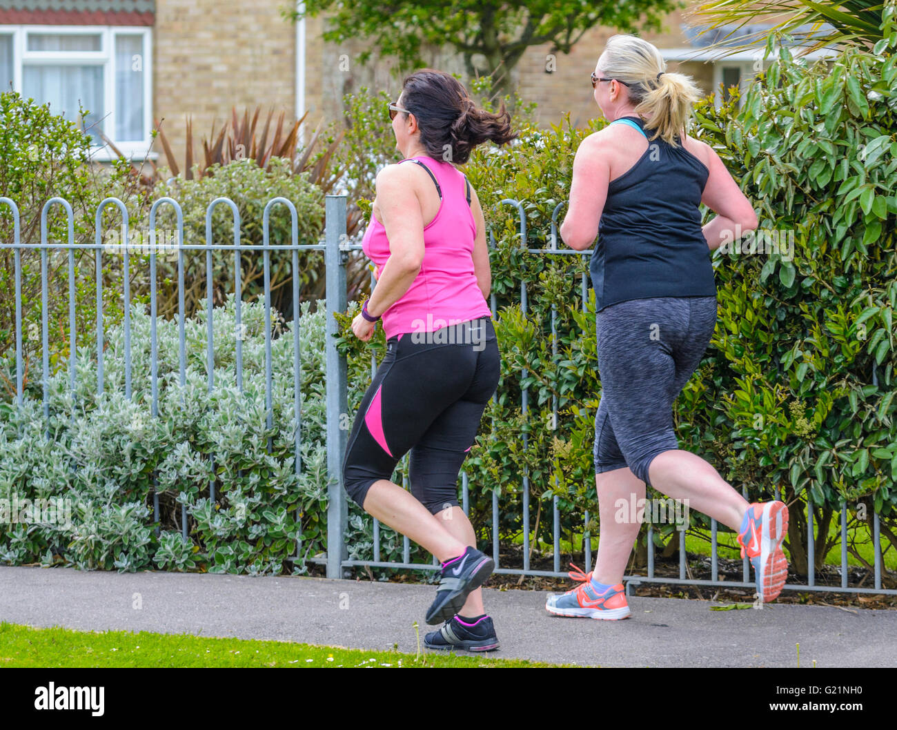 Pair of female joggers on a residential street in the UK. - Stock Image