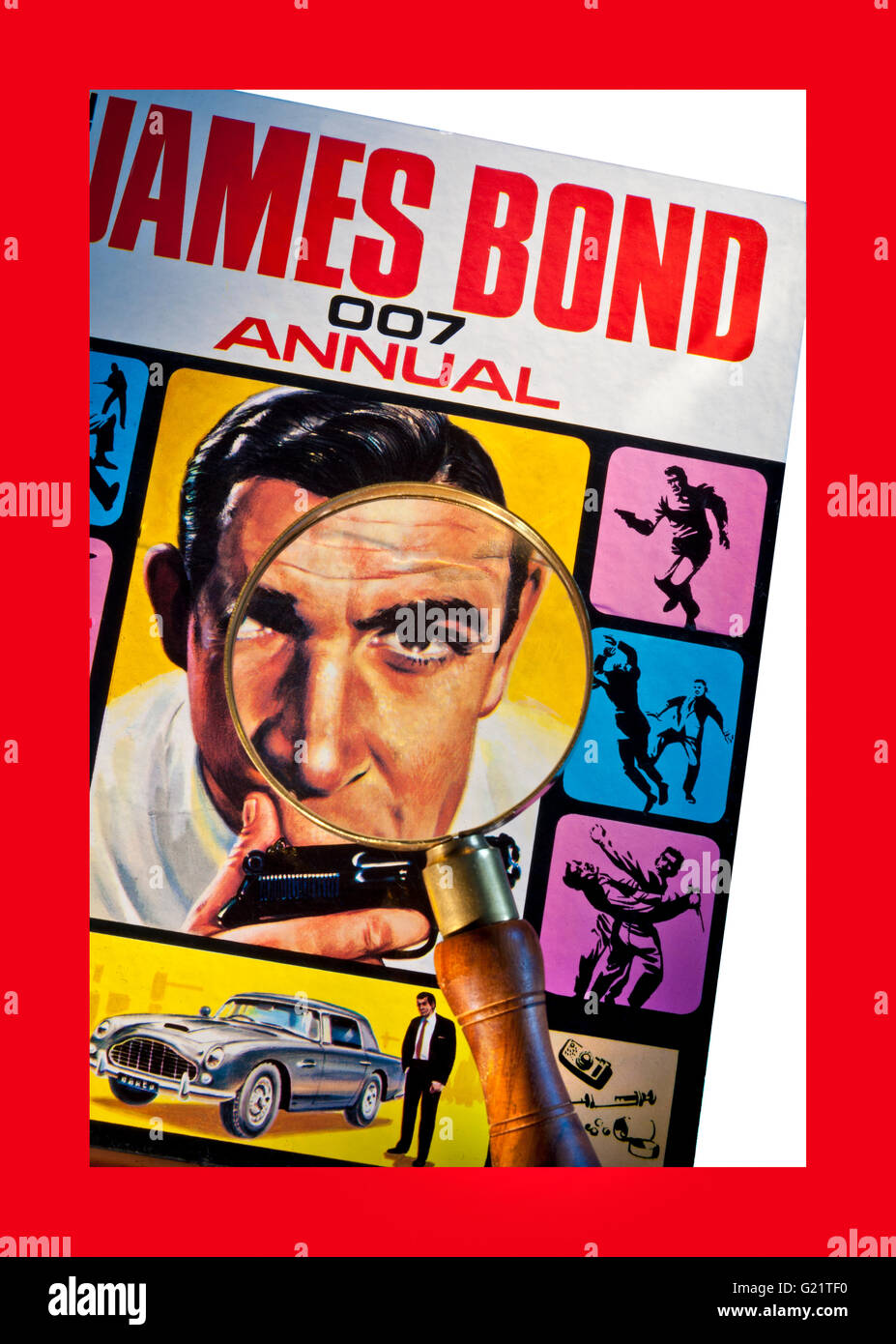 Magnifying glass on detail of 1965  'The James Bond 007 Annual' Sean Connery with Walther PPK gun and Aston - Stock Image