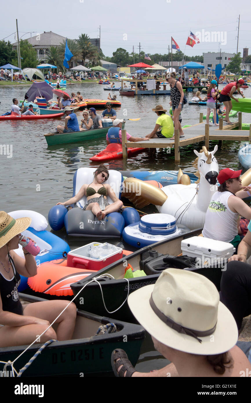 Sunbathers along the edge of bayou St John during the Bayou Boogaloo festival. - Stock Image