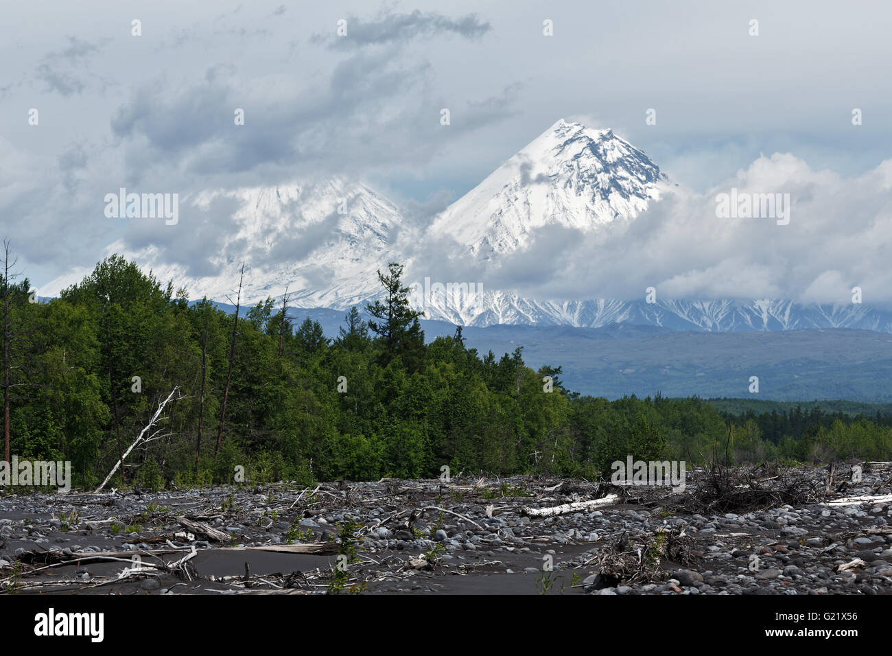 Beautiful summery view on Klyuchevskoy Volcano (in the clouds) and Kamen Volcano on a cloudy day. Russia, Far East, - Stock Image