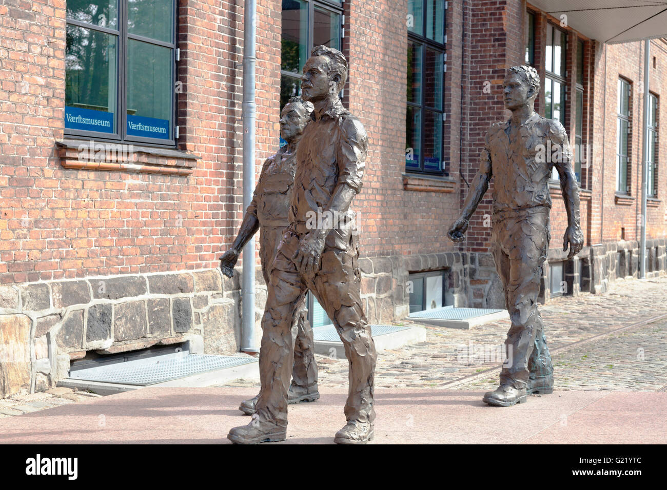 Bronze sculpture of three broad- shouldered shipyard workers on their way to the entrance to the Elsinore shipyard, - Stock Image
