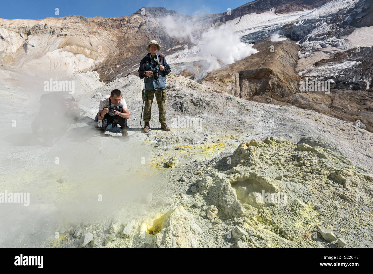 Photographers in crater Mutnovsky Volcano near active sulfur fumaroles, ejecting steam and gas. Kamchatka Peninsula. - Stock Image