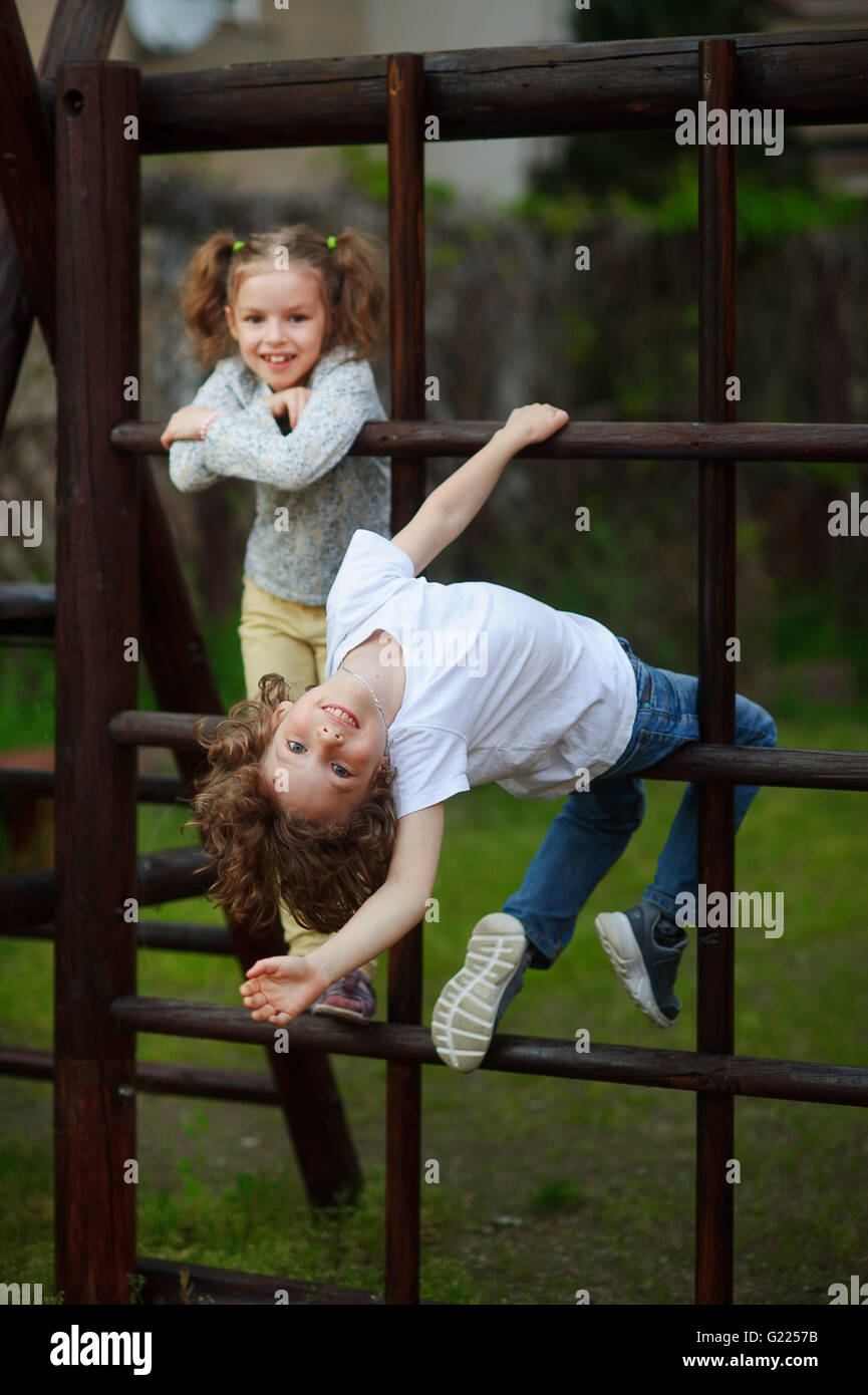 Two children climb on the bars while playing in the yard - Stock Image
