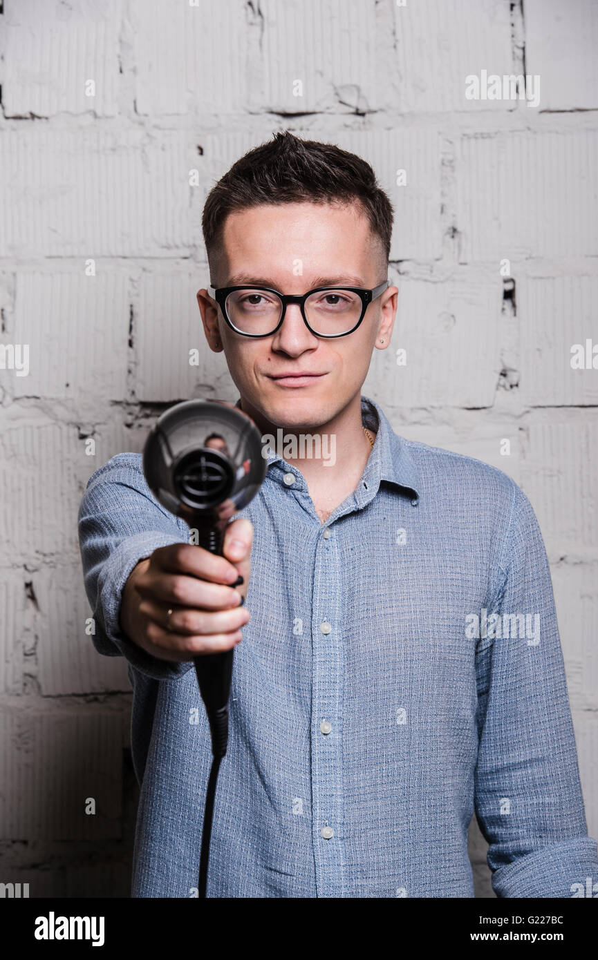 Male stylish hairdresser holding a blow dryer and shooting to the camera over grey brick wall - Stock Image