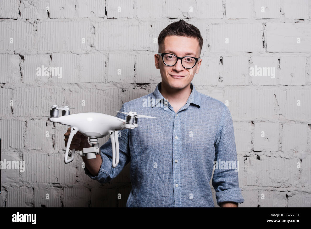 Young stylish Man in glasses with quadcopter drone on a grey brick wall Stock Photo