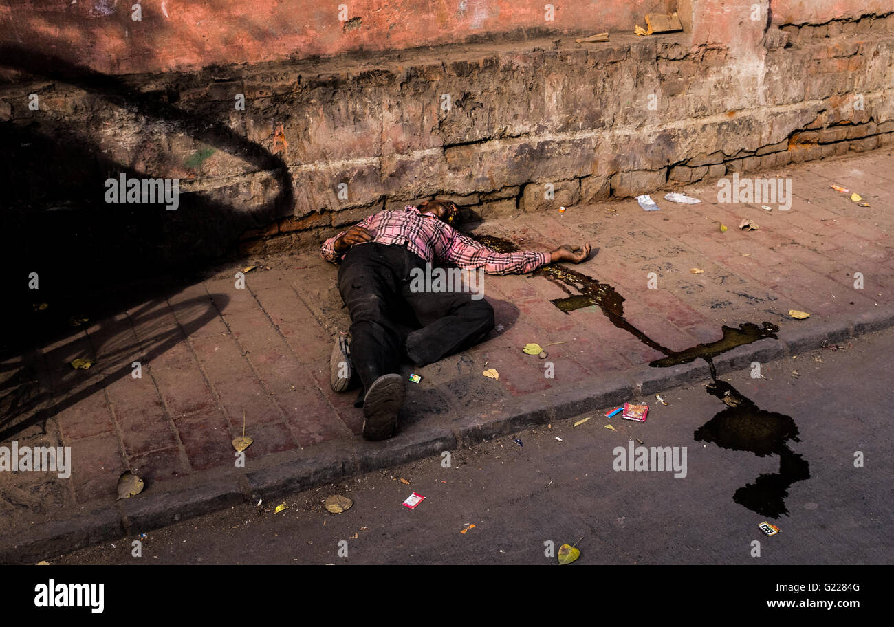 Man passed out on pavement having been sick, Delhi, India. - Stock Image