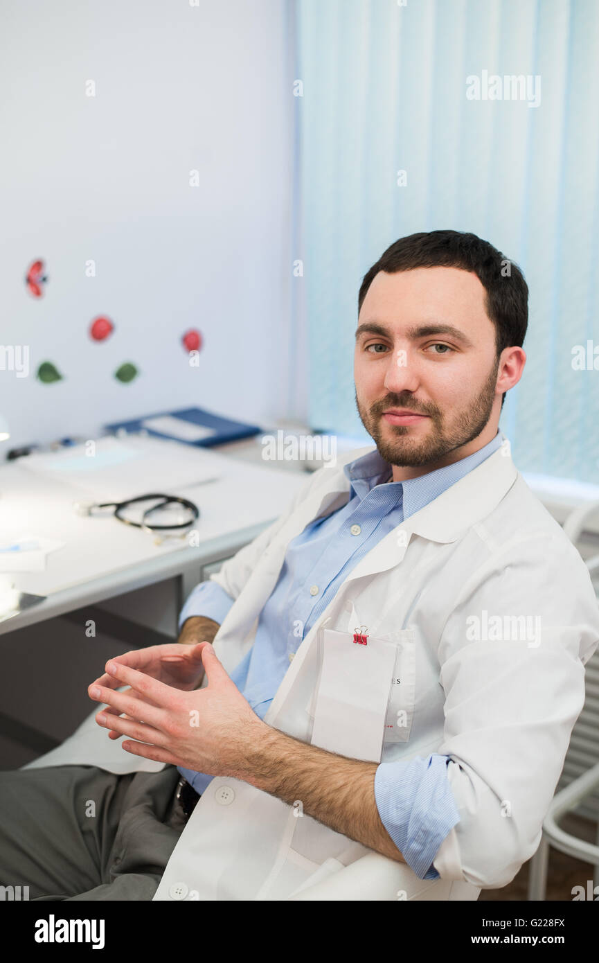 Calm doctor or consultant sitting at desk with his stethoscope on  table looking to the camera - Stock Image