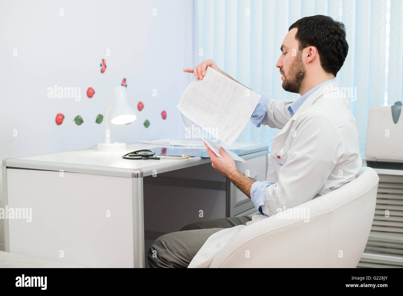 Doctor working with test results of his patient at office - Stock Image