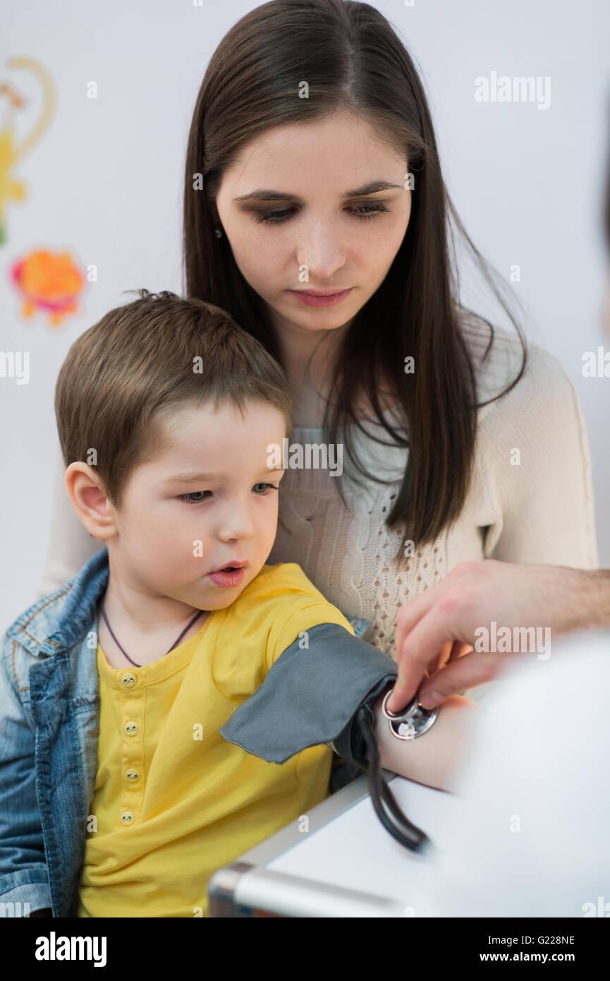 Little boy medical visit - doctor measuring blood pressure of a child - Stock Image
