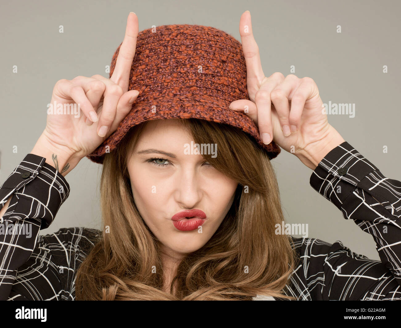 Portrait of A Woman Being or Acting Silly Pulling Faces and Acting the Fool With Finger Gestures and Humorous Facial - Stock Image