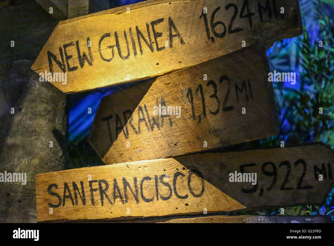 wooden arrow signs indicating the direction of various places and distances in miles - Stock Image