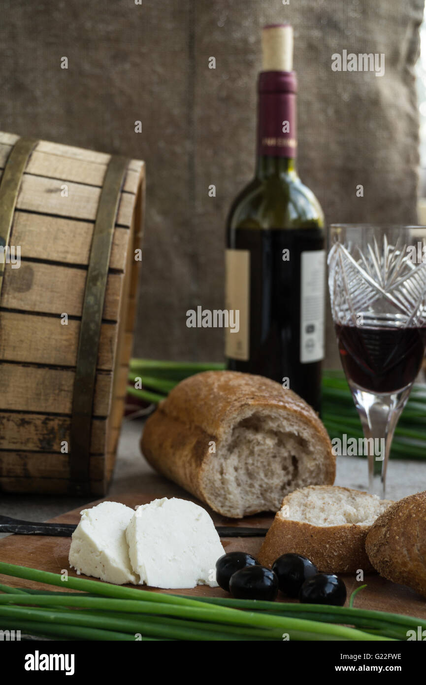 Octave, wineglass, bread and cheese are on sacking - Stock Image